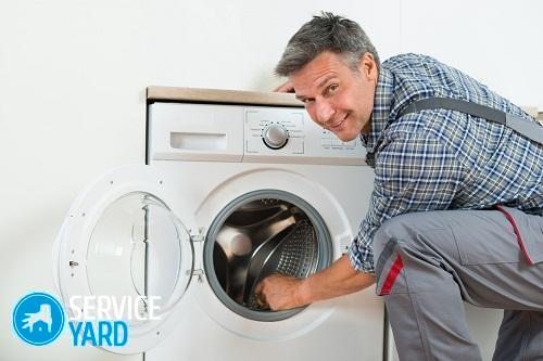 Side view of repairman checking washing machine at home