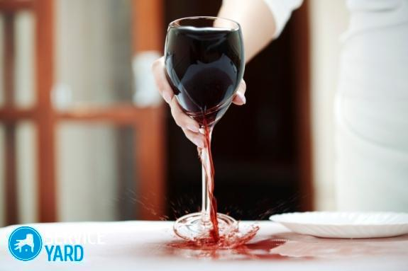 Waitress spilling red wine to white tablecloth at restaurant