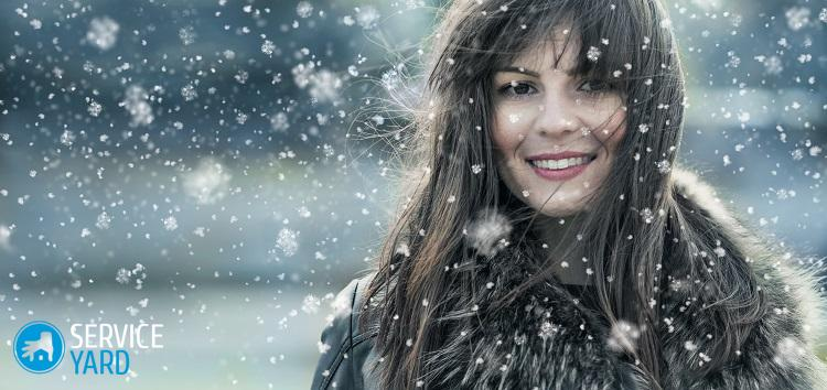 Beautiful young woman in a winter snow day. Girl wearing fur and looking to camera trough snowflakes. Copyspace