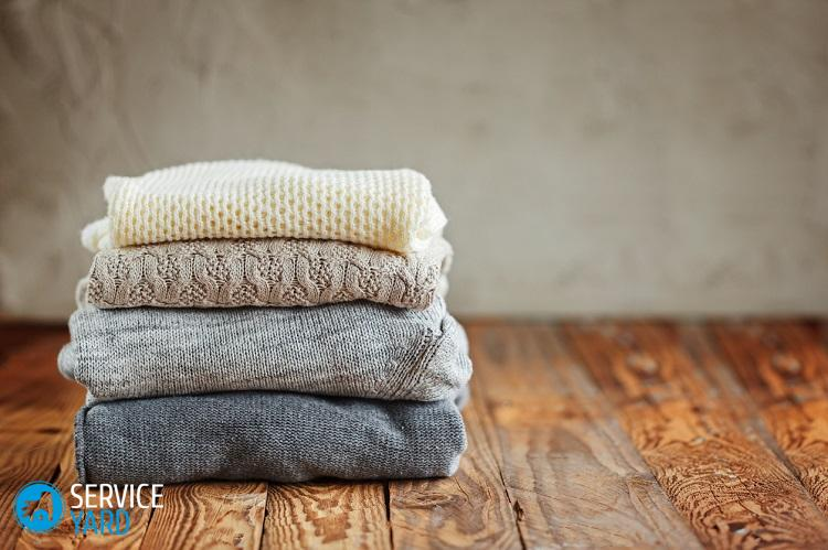 Stack of knitted winter clothes on wooden background, sweaters, space